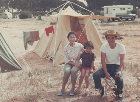 Hirahara at around six years old during her family's regular summer camping trips along the California coast. Her mother Mayumi is on the left and father Isamu is on the right. Her younger brother, Jimmy, was born when she was eight and a half years old.
